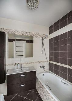 Törtfehér és szürkésbarna padló és falburkolatok, utóbbi mintás és mozaik elemekkel, barna bútor fürdőkád