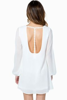 An ethereal shift dress featuring a deep scoop cut back with daisy appliques. Deep v-neck. Long elasticized sleeves with side slits. Finished short hem. Fully lined.