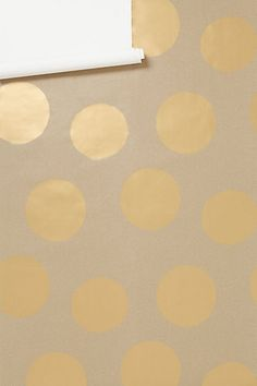 Luxe Shine Wallpaper - Anthropologie.com... Kraft paper with gold dots. They're charging $200 for 30 square feet. I'm fairly sure we could craft that for a LOT less.... Maybe line the back of a bookcase?