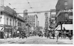 Looking Down 12th Street - view looking west down 12th Street from around Grand Ave.  Street is full of horse and buggies, one automobile, a streetcar and people strolling.  The Jones Store is visible farther down the street at 12th and Main. 1910