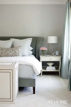 Tranquil Bedroom with gray-blue walls, silk curtains, gray upholstered headboard, nailhead-trimmed pouff and white linens and furniture - Edgehill home by Kevin Walsh of Bear-Hill Interiors, via At Home in Arkansas