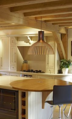 Breakfast bar on the end of a central kitchen island, oak floor joists above.