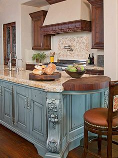 Tuscan kitchens are known for attention to detail and handcraftsmanship, with notable features like this kitchen's carved island corbels and wood range hood embellishments. Incorporate ornate and furniturelike details on cabinetry, freestanding pieces, and woodwork in your own kitchen for the perfect Tuscan touch.
