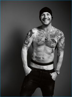 A shirtless Tom Hardy delivers a cheeky grin as he sports a wool hat and black denim jeans by Gucci.