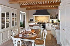 Klasyczna kuchnia w stylu prowansalskim: białe krzesła, stół, witryna z szafkami oraz okap