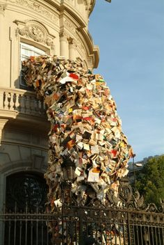 Photograph of an art installation series presenting buildings around Madrid pouring out thousands of books, by Spanish artist Alicia Martin