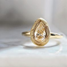 A prism of transformative light radiates from this pear cut diamond, nestled in a feather inspired halo. She's a nest egg of transformative beauty and divine creativity. Sits low profile in her ultra chic 14k yellow gold setting.