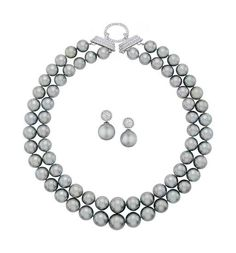 A Cultured Pearl and Diamond Suite  Comprising a necklace, designed as two graduated strands of Tahitian cultured pearls, measuring from approximately 11.20 to 13.20 mm, joined by a circular-cut diamond clasp; a pair of circular-cut diamond earclips en suite suspending a detachable Tahitian cultured pearl drop, mounted in 18K white gold, necklace length 17 inches to 19 inches, earclips length 1 inch.