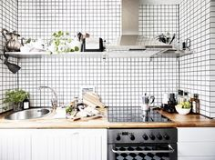 Scandinavian kitchen with grid tile walls, cutting boards, open shelves, and wood counters