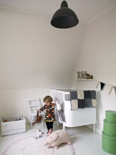 Scandinavian kid's room. White floors, walls and furniture. Black contrasts. green accent.