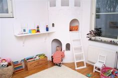 A play castle by VeraVera. We love the cozy nook underneath for quiet moments and the second floor balcony accessible by ladder. It's a great room within a room that doesn't take up too much floor space.