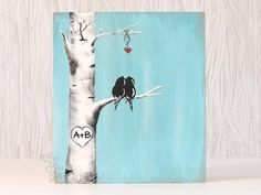 """This painting features a cute little pair of love birds perched in an Aspen Tree / birch tree. A heart hanging above symbolizes the love between the pair. This painting would make a great wedding, 5th anniversary, or engagement gift!  DIMENSIONS:13"""" x 11 1/2"""", on wood, wire hanger attached. The one with the blue b"""