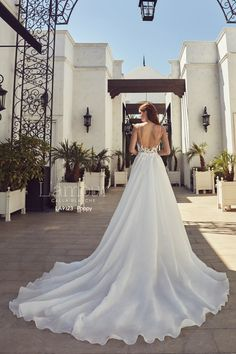 a568cb16938 Stunning long train falls off the low back of this wedding dress.