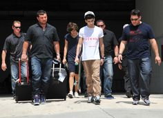 Zayn, Harry and security leaving the hotel yesterday!....skateboard?