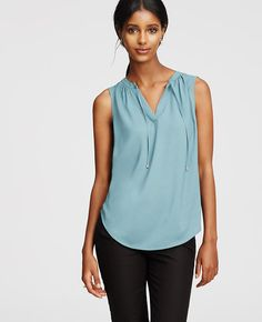 Tipped with shimmery metallics, we're into this top pick of the season. Split neck with shirred mandarin collar and metallic-tipped ties. Sleeveless. Shirttail hem.