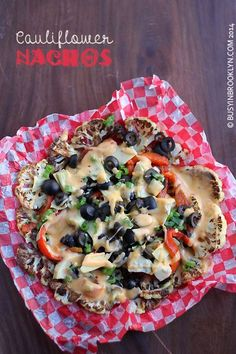 "Cauliflower Nachos - a healthy twist on traditional nachos with roasted cauliflower ""chips"", roasted red peppers, artichokes, black olives, scallions and a harissa cheddar nacho cheese sauce."
