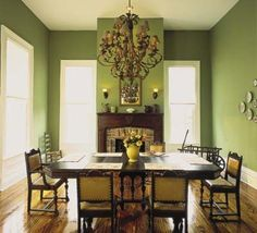 Opt for bright and cheery walls that contrast nicely with dark Victorian furniture, like this moss green dining room.