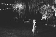 Late night kiss under cafe lights and the oaks. Sequined halter Jenny Packham bridal gown. Wedding colors of plum and wine. Vintage style wedding at Magnolia Plantation photographed by Charleston wedding photographer Priscilla Thomas.