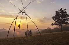 Picture of girls in traditional dress playing on a handcrafted swing at sunrise in Thailand