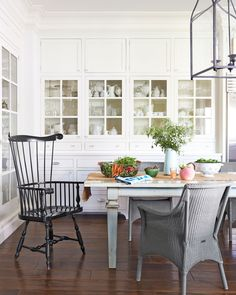 """A warm, community-oriented lifestyle was top of mind when Blazona designed her home: The 20-by-30-foot """"dream kitchen"""" has a farmhouse table that seats 12. In this photo: Blazona's kitchen built-ins hold all her ironstone and glassware. The Windsor chair is by Ethan Allen; the wicker seats are Janus et Cie. White Dove by Benjamin Moore covers the walls."""