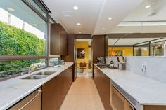 Nab a Late-Career Work by a Palm Springs Modernist for $1.6M - House of the Day - Curbed National Kitchen above living area - bench bcomes seperating wall