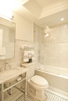 Elegant bathroom features small tray ceiling over mosaic tiled drop-in bathtub accented with two-tone tiles: mosaic tiles on top part of walls and large marble subway tiles on bottom part of walls as well as glass shower partition.