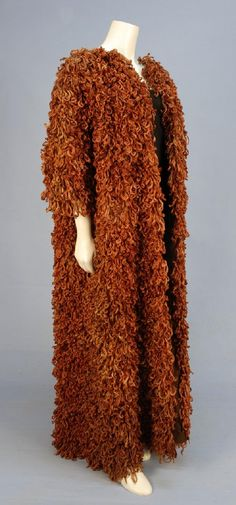 BALENCIAGA COUTURE SILK COAT, AUGUST 1963. Brown organdy over a stiffened net inter- liner, organdy lining, having three quarter sleeve covered allover in applied pieces of shredded and torn rust silk faille, no closures. Label: Balenciaga 10, Avenue George V. Paris. Bust 50, length 56. (Some losses and fading, some splits to organdy outer layer) fair.