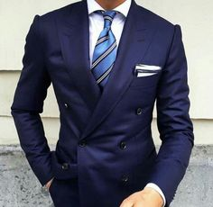 Beautiful double breasted navy suit. A lite blue striped tie, white pocket square with navy edges. None of the extras take away from the beauty of the suit.