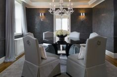 Nice gray dining room with textured paint, gauzy drapes and crystal chandelier...nice chairs or chair slipcovers as well...