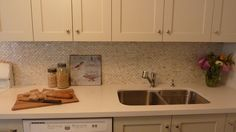 Beautiful kitchen with cream cabinets painted Benjamin Moore natural Cream paired with off-white quartz countertop and Olympia Tile Mother of pearl Mosaic Tile backsplash. Cream Shaker Kitchen, White Kitchen Counters, Cream Kitchen Cabinets, Quartz Kitchen Countertops, Kitchen Flooring, Kitchen Backsplash, White Cabinets, Kitchen Mosaic, Mosaic Backsplash