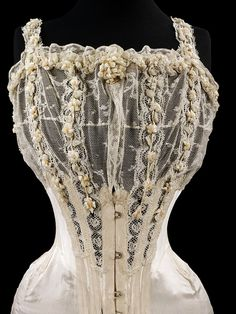 Wedding Corset from the UK. Credit Line: Worn and given by Mrs G. E. Dixon Museum number: T.90-1928 This corset was designed and made for the wedding of Mrs G.E. Dixon in July 1905. It is an S-bend corset, typified by the straight busk that compelled the pelvis backwards and the bust forwards into an angled 'S' shape. Vintage Corset, Vintage Lingerie, Vintage Lace, Vintage Dresses, Vintage Outfits, Victorian Corset, Victorian Era, Wedding Corset, Bridal Corset