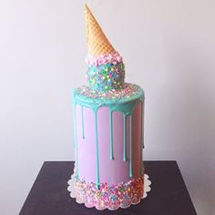 To decorate it, ice with purple dyed buttercream, then layer on fondant and smooth. While moist, press on sprinkles around base. then add ball on top. Drizzle blue dyed melted chocolate over ball. While wet, lightly add sprinkles and cone.