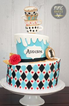This Alice in Wonderland cake is definitely one of my favorites! I love the baby blue mixed with the red hearts and black diamonds. The top tier is a 6″, and the bottom tier is a 10″.…