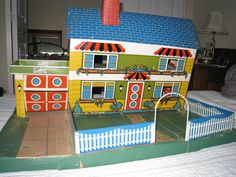 "1950s Eagle Canada tin litho dollhouse DH-408. Front view. ""The box becomes the yard""  The garage door lifts up and down."
