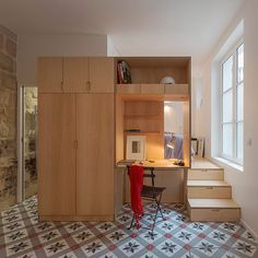A birch-plywood unit separates the bedroom from the living space in this Parisian studio, located inside a 17th-century townhouse.  To squeeze extra living space out of the compact apartment, architect Anne Rolland also converted a former slurry pit below it into a music room and home cinema. See more apartments that make the most of every square inch on dezeen.com/tag/apartments #architecture #interiordesign #interiors #apartments
