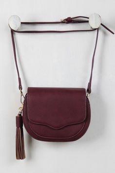 This sling bag features a textured vegan leather throughout, detachable tassel, top zipper closure, magnetic snap closure flap, outer pocket and one zipped pocket inside. Finished with an adjustable b