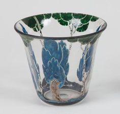 Vase en verre transparent, de forme évasée à large ouverture. Décor tournant d arbres traités en émaux durs de couleur contrastées bleu, vert, blanc et noir. Signature émaillée M. Goupy sous la base