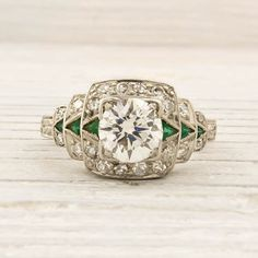 Emerald and diamond ring, circa 1925. Set in PLATINUM and centered with an approximate .79 CARAT EGL certified old european cut diamond with F-G color and VS1 clarity. Center diamond is accented with triangle cut emeralds and single cut diamonds