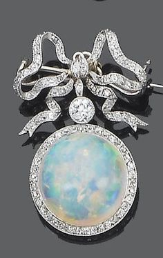 A Belle Epoque opal and diamond brooch, circa 1905. The single-cut diamond tied ribbon bow suspending an old brilliant-cut diamond and a circular cabochon opal with a single-cut diamond border, mounted in silver and gold, detachable brooch fitting. #BelleÉpoque #brooch