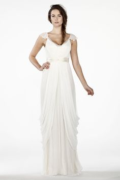 """Romantic sheer v-neck silk chiffon dress with delicate flutter sleeves and elegant side draped skirt that will perfectly compliment a feminine bride.  • Can be accessorized with many sashes and belts from our accessory page. Made of 100% silk: • Top layer: Off white silk chiffon • Lining: Cream silk charmeuse. • Comes with 2"""" wide cream silk charmeuse sash. • Should be worn with a strapless bra.Please refer to our sizing chart to make accurate measurements and find your size. For any…"""