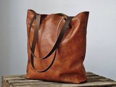 Cognac leather tote bag: lightweight and roomy - ideal for use as a shopper (fold-able and easy to store) or to carry your essentials in style. Made with a vintage-look, upholstery-weight leather it is light and perfect for on-the-go, or as a bag for shopping expeditions. Natural suede lining with triple stitched seams for strength at the base corners. Brown leather straps and antique-look rivets.  Optional zipper pouch pocket for valuables.  Caramel version available here: https://...