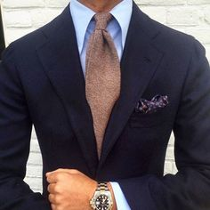 Navy jacket, light blue shirt, light brown tie