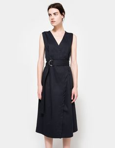 From NEED, a lightweight twill dress in Navy. Featuring a v-shaped neckline, nickel D-ring hardware at belt, exaggerated belt length, interior snap closures, lux Japanese twill tape finishing, cotton grosgrain binding at inside waist seam, angled edge at