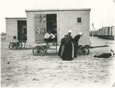Strand met op de voorgrond een badkoets in gebruik als bewaarplaats voor badgoed; rechts een rij badkoetsen die gebruikt werden als verkleedkabines. ca 1925 H. Berssenbrugge #ZuidHolland #Scheveningen