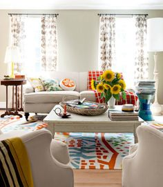 The owner of this Maine home splashed colorful vintage pieces as well as bold and boisterous pillows—pink bunnies, green squirrels, orange flowers—to add color to her living room. The handwoven rug is by area artisan Angela Adams.