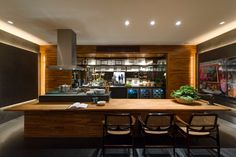 A madeira do revestimento e da mesa se alinha ao cinza da ilha do fogão, prateleiras e do piso.