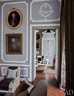 Beneath two antique portraits in the living room stands a 1940s Carlhian armchair upholstered in linen by Romo. Deniot ennobled the space, and the library beyond, with neoclassical-style architectural details.