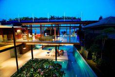Fachada moderna, casa de singapur, casa con techo en hierva, algo que realmente le brinda un detalle de lujo y excéntrico a esta casa moderna de playa.