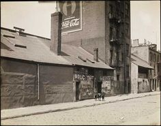 Old wood-frame building on West and Weehawken streets, and today's West Side highway. Image from MCNY