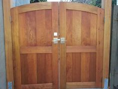 An exterior view of a double outswinging gate with the Moda Stainless Steel Contemporary Gate Latch and Dummy Handle. Deadbolt installed above.        View from Exterior of Outswinging Double Gate with Dummy Handle. 360 Yardware.